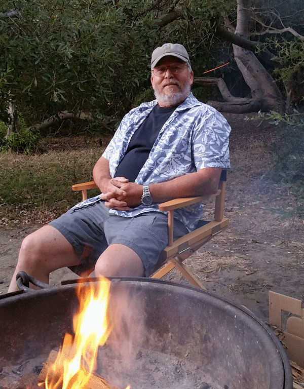 Hubby sitting by the fire in our campground at San Simeon State Park